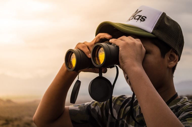 Man looking through binoculars as a metaphor for what to look for while buying swivel keyboard tray