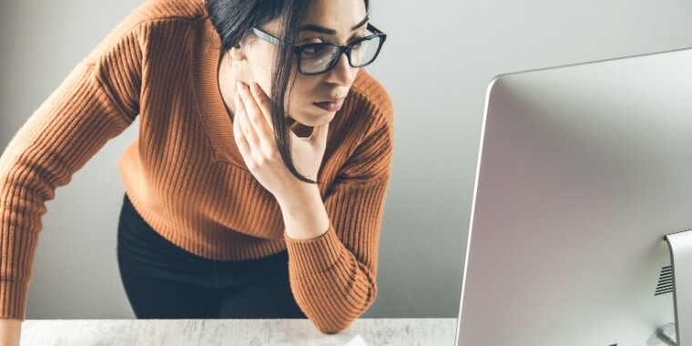Woman looking for a cause of green pixels on her monitor