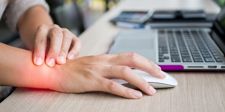 A hand using mouse without a mouse pad and this is causing wrist pain (wrist is highlighted in red to point user attention on the pain)