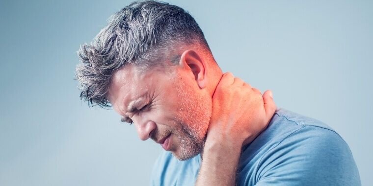 A man holding his neck because of pain that is caused by absence of office chair for neck support