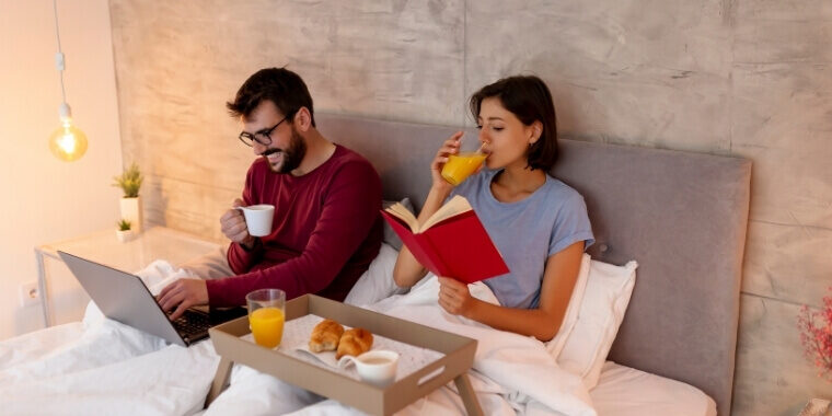 Couple reading in bed using regular pillows. They obviously miss a back support for their reading in bed session