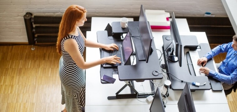 A woman using a height adjustable desk with keyboard tray at work